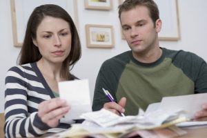 Concerned couple looking over bills working to help rebuild bad credit.
